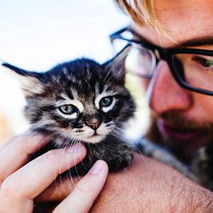 cuidador de gatos con cachorro en sus manos